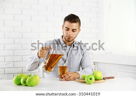 Young man man pouring apple juice into glass - stock photo