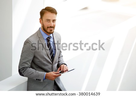 Young man manager in good mood holding touch pad while standing in hallway company near copy space area, smiling male prosperous and successful banker with digital tablet in hands look at the camera  - stock photo