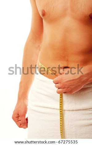 Young man measuring his waist - stock photo