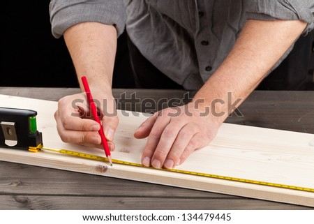 Young man measuring wooden plank - diy or home renovation concept - stock photo