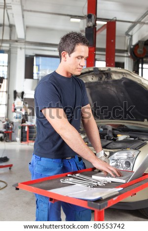 Young man mechanic using a laptop in a auto repair shop - stock photo