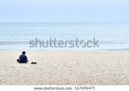 young man meditating at the sea