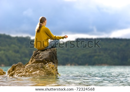 Young man meditating on a rock