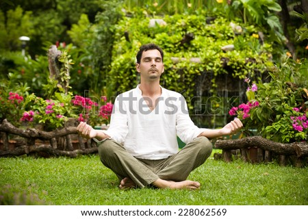 Young man meditating surrounded by tropical trees and bushes - stock photo