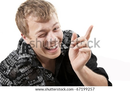 young man miles and points a finger upwards - stock photo
