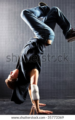 Young man modern dance. On dark wall background. - stock photo