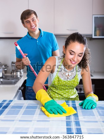 Young man mopping and smiling woman dusting in domestic kitchen - stock photo