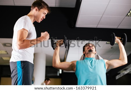 Young man motivating gym buddy during shoulder exercise - stock photo