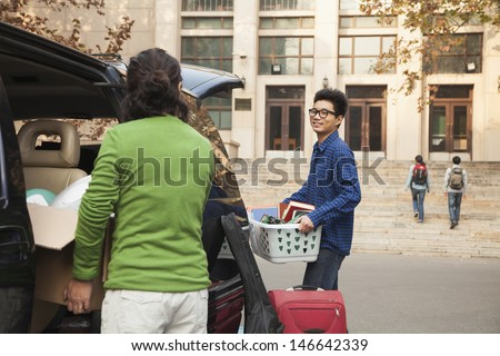 Young man moving into dormitory on college campus - stock photo