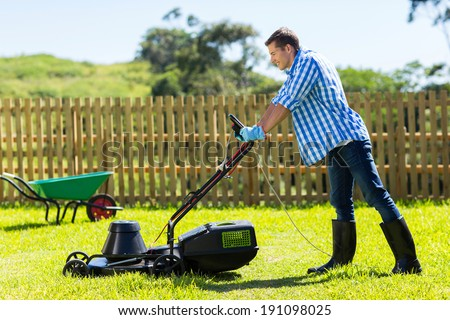 young man mowing lawn at home - stock photo