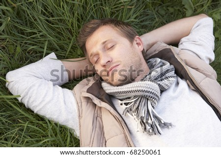 Young man napping alone on grass - stock photo