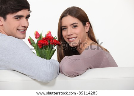 young man offering a bouquet of  flowers to his girlfriend