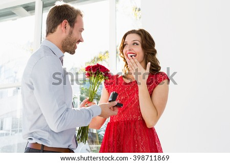 Young man offering flowers and engagement ring to beautiful woman - stock photo