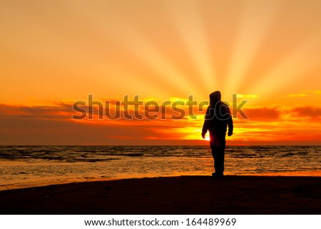 young man on a beach at sunset