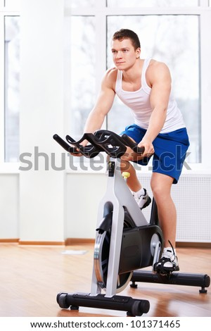 Young man on a bicycle simulator - stock photo