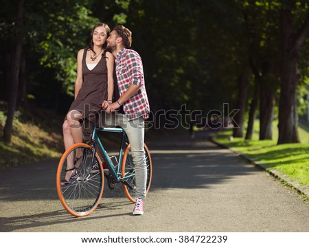 Young man on a bicycle  whispers sweet words to his girlfriend  that sits on the bicycle fork with eyes closed - stock photo