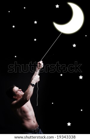 young man on a black background try to catch crescent - stock photo