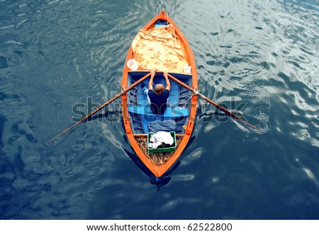 Young man on a boat : rowing fisherman - stock photo