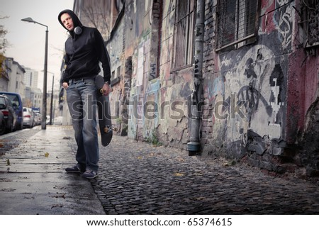 Young man on a city street holding a skateboard - stock photo