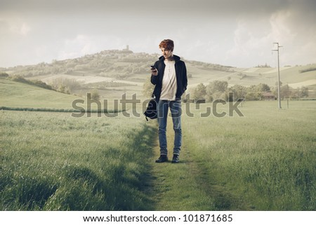 Young man on a country pathway carrying a rucksack and using a mobile phone - stock photo