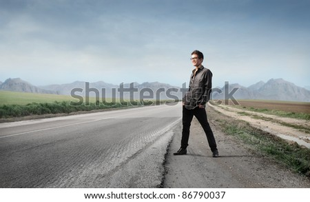 Young man on a countryside road - stock photo