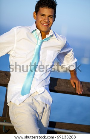 Young man on a pier in a tie at sunset - stock photo