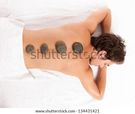 young man on a spa getting a hot stone massage. studio shot. - stock photo