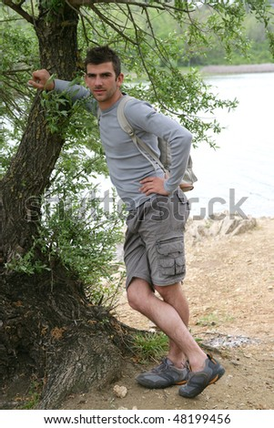 Young man on a trekking day resting by a tree