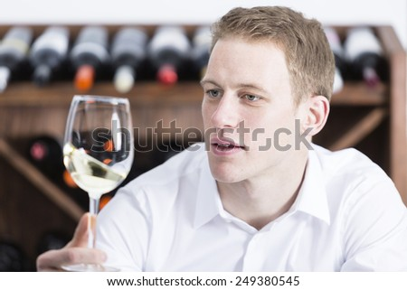young man on a wine tasting session on the olfactory phase is analyzing the white wine shaking the wineglass at a restaurant - focus on the man face