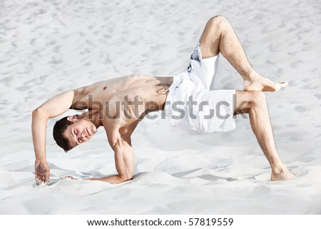 Young man on beach. Bright white colors. - stock photo