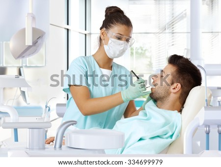 Young man on dental check-up, examined by female dentist. - stock photo