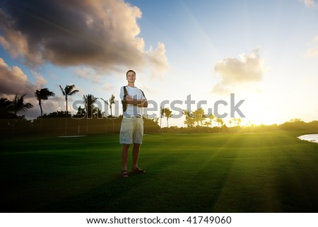 young man on green field and sunset