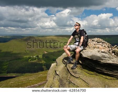 Young man on mountain peak - stock photo