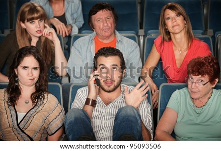 Young man on phone disturbs people in theater - stock photo