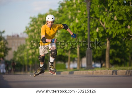 Young man on rollerblades skating at park