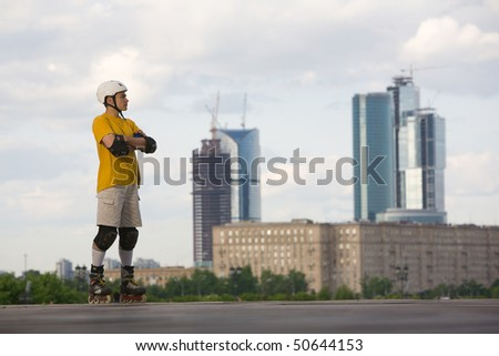 Young man on rollerblades standing at looking at urban view - stock photo