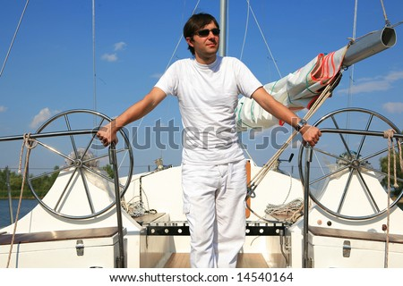 Young man on sailboat desk looks ahead. - stock photo