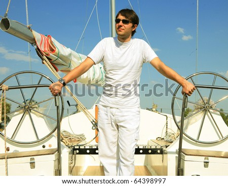 Young man on sailboat desk looks ahead - stock photo