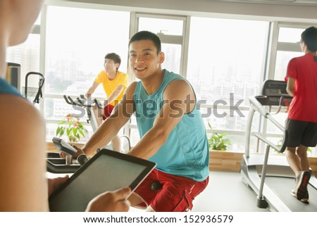 Young man on stationary bike exercising with his personal trainer - stock photo