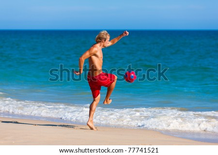 Young man on the beach playing soccer in his vacation - stock photo