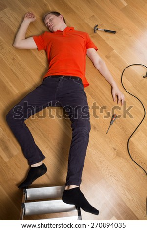 Young man on the floor having dangerous accident at home - stock photo
