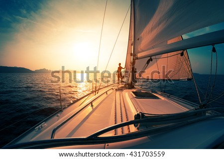 Young man on the sailing boat at sunset - stock photo
