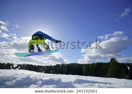 young man on the snowboard jumping over the slope in winter - stock photo
