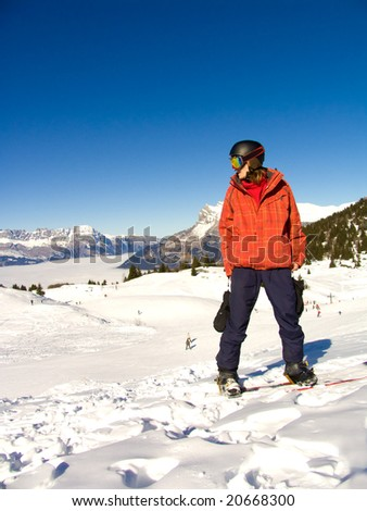 Young man on the snowboard under the bright sun