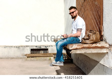 Young man on the street posing on camera. Walk in the city. Portrait in sunglasses. Chat in social networks.  - stock photo