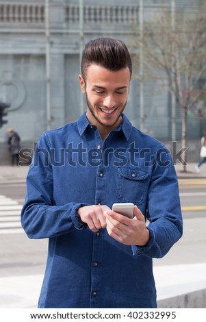 Young man on the street using a smart phone - stock photo