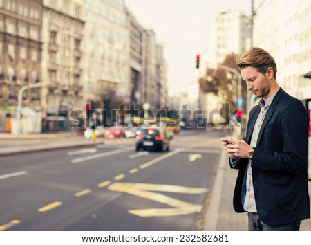 Young man on the street with mobile phone - stock photo