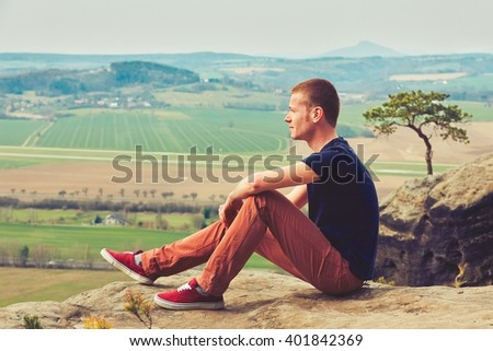 Young man on the top of the rock  - stock photo