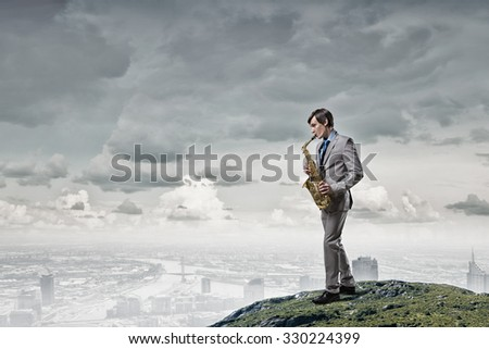 Young man on top of rock playing saxophone
