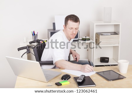 young man on wheelchair working in a office, using a tablet computer and a laptop computer. - stock photo